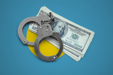 Palau flag  with handcuffs and a bundle of dollars. Currency corruption in the country. Financial crimes.
