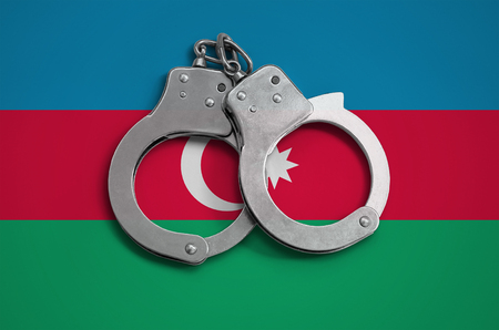 Azerbaijan flag  and police handcuffs. The concept of observance of the law in the country and protection from crime. Stock Photo