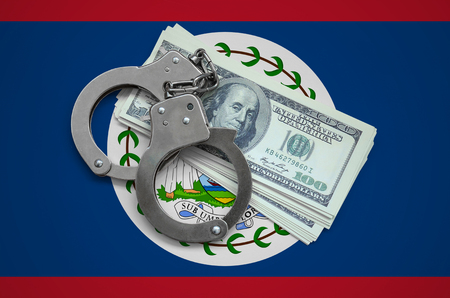 Belize flag  with handcuffs and a bundle of dollars. Currency corruption in the country. Financial crimes. 版權商用圖片