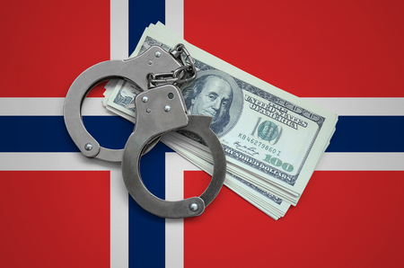 Norway flag  with handcuffs and a bundle of dollars. Currency corruption in the country. Financial crimes. Фото со стока