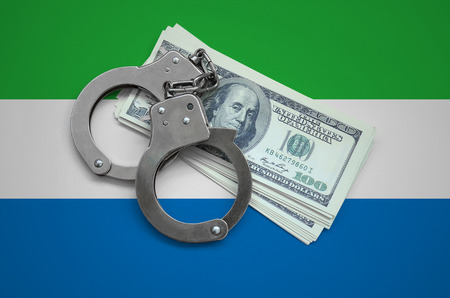 Sierra Leone flag  with handcuffs and a bundle of dollars. Currency corruption in the country. Financial crimes.