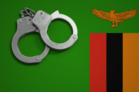 Zambia flag  and police handcuffs. The concept of crime and offenses in the country. Stock Photo