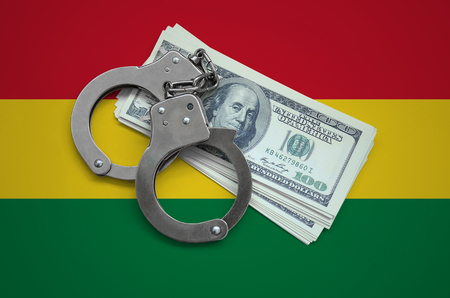 Bolivia flag  with handcuffs and a bundle of dollars. Currency corruption in the country. Financial crimes.
