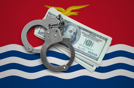 Kiribati flag  with handcuffs and a bundle of dollars. Currency corruption in the country. Financial crimes.