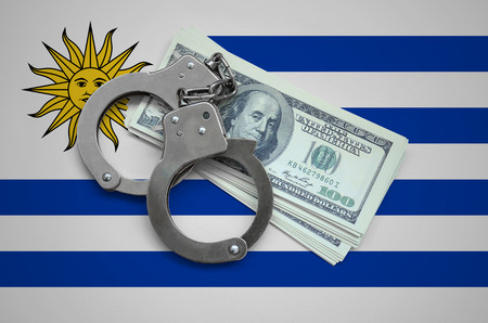Uruguay flag  with handcuffs and a bundle of dollars. Currency corruption in the country. Financial crimes.
