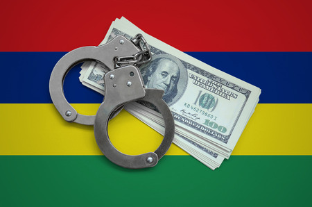 Mauritius flag  with handcuffs and a bundle of dollars. Currency corruption in the country. Financial crimes.