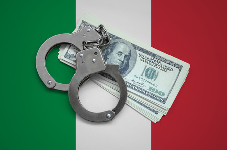 Italy flag  with handcuffs and a bundle of dollars. Currency corruption in the country. Financial crimes.