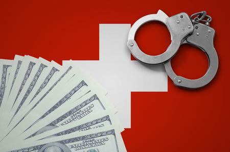 Switzerland flag  with handcuffs and a bundle of dollars. The concept of illegal banking operations in US currency.