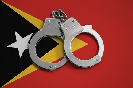 Timor Leste flag  and police handcuffs. The concept of observance of the law in the country and protection from crime. Stock Photo