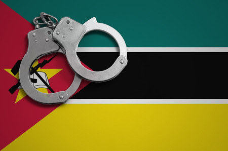 Mozambique flag  and police handcuffs. The concept of crime and offenses in the country. Reklamní fotografie