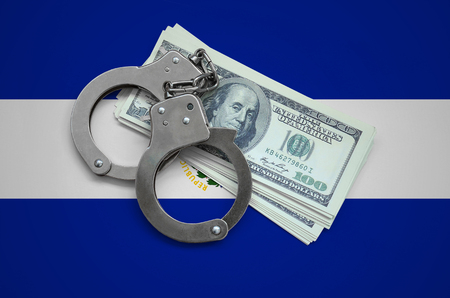 El Salvador flag  with handcuffs and a bundle of dollars. Currency corruption in the country. Financial crimes. Фото со стока