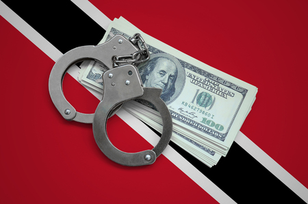Trinidad and Tobago flag  with handcuffs and a bundle of dollars. Currency corruption in the country. Financial crimes.