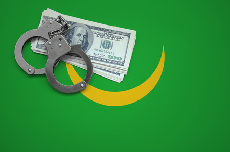 Mauritania flag  with handcuffs and a bundle of dollars. The concept of breaking the law and thieves crimes. Stock Photo