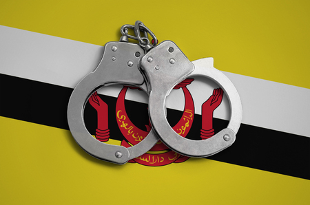 Brunei Darussalam flag  and police handcuffs. The concept of observance of the law in the country and protection from crime. Stock Photo