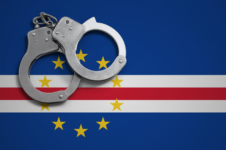 Cabo verde flag  and police handcuffs. The concept of crime and offenses in the country.
