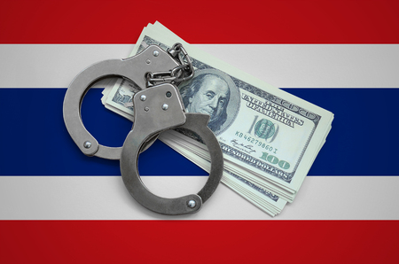 Thailand flag  with handcuffs and a bundle of dollars. Currency corruption in the country. Financial crimes.