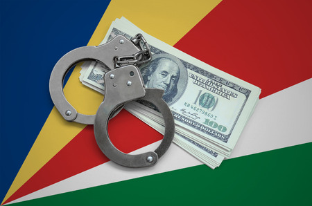Seychelles flag  with handcuffs and a bundle of dollars. Currency corruption in the country. Financial crimes. 版權商用圖片