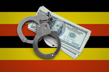 Uganda flag  with handcuffs and a bundle of dollars. Currency corruption in the country. Financial crimes. 版權商用圖片