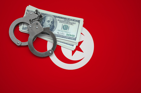 Tunisia flag  with handcuffs and a bundle of dollars. The concept of breaking the law and thieves crimes.