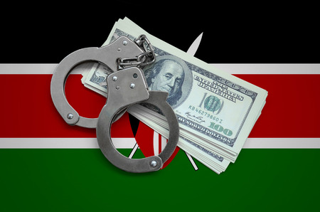 Kenya flag  with handcuffs and a bundle of dollars. Currency corruption in the country. Financial crimes.