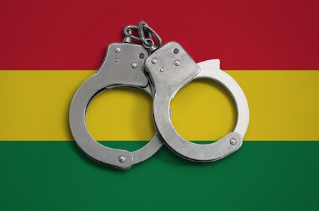 Bolivia flag  and police handcuffs. The concept of observance of the law in the country and protection from crime.