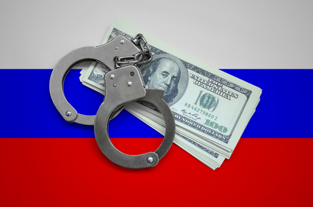 Russia flag  with handcuffs and a bundle of dollars. Currency corruption in the country. Financial crimes.