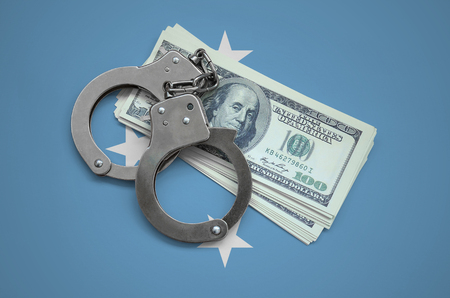 Micronesia flag  with handcuffs and a bundle of dollars. Currency corruption in the country. Financial crimes.