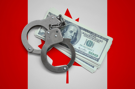 Canada flag  with handcuffs and a bundle of dollars. Currency corruption in the country. Financial crimes.