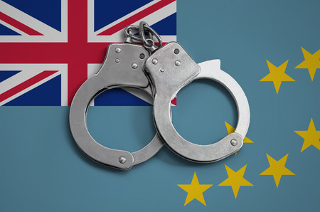 Tuvalu flag  and police handcuffs. The concept of observance of the law in the country and protection from crime.