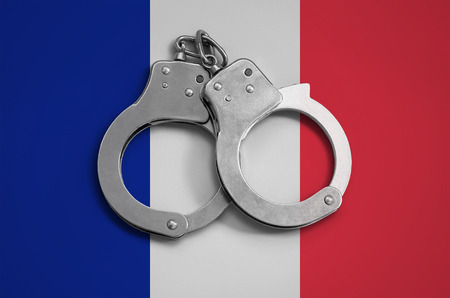 France flag  and police handcuffs. The concept of observance of the law in the country and protection from crime.