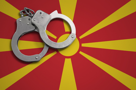 Macedonia flag  and police handcuffs. The concept of crime and offenses in the country. Фото со стока