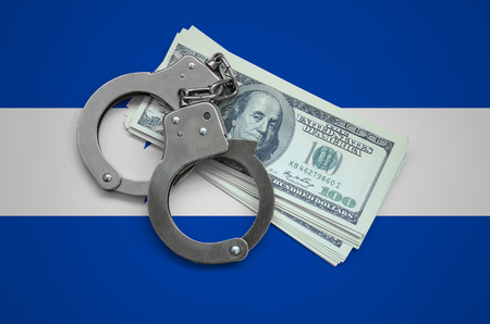 Honduras flag  with handcuffs and a bundle of dollars. Currency corruption in the country. Financial crimes. Фото со стока