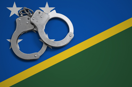 Solomon Islands flag  and police handcuffs. The concept of crime and offenses in the country.