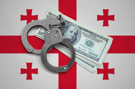 Georgia flag  with handcuffs and a bundle of dollars. Currency corruption in the country. Financial crimes.