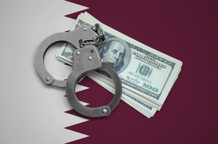 Qatar flag  with handcuffs and a bundle of dollars. Currency corruption in the country. Financial crimes. 版權商用圖片