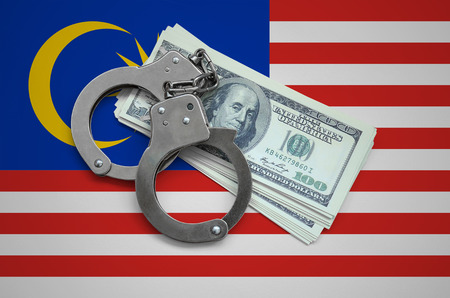 Malaysia flag  with handcuffs and a bundle of dollars. Currency corruption in the country. Financial crimes.