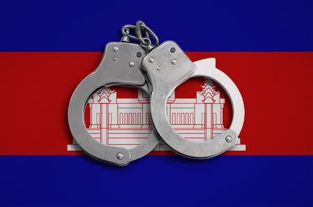 Cambodia flag  and police handcuffs. The concept of observance of the law in the country and protection from crime. Stock Photo
