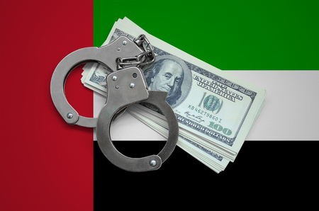 United Arab Emirates flag  with handcuffs and a bundle of dollars. Currency corruption in the country. Financial crimes.