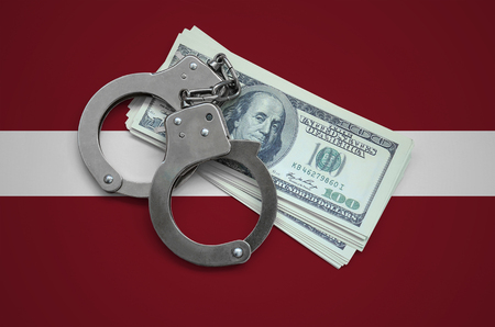 Latvia flag  with handcuffs and a bundle of dollars. Currency corruption in the country. Financial crimes. 版權商用圖片