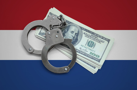 Netherlands flag  with handcuffs and a bundle of dollars. Currency corruption in the country. Financial crimes.