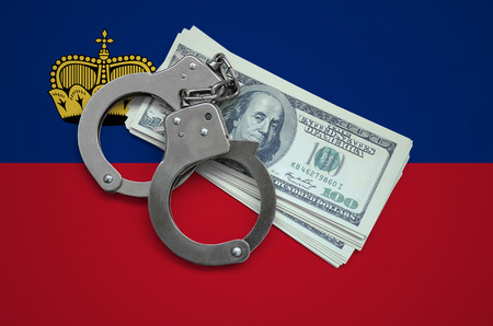 Liechtenstein flag  with handcuffs and a bundle of dollars. Currency corruption in the country. Financial crimes. 스톡 콘텐츠