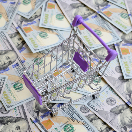 Empty small shopping cart lies on a many dollar bills.