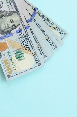 US dollar bills of a new design with a blue stripe in the middle is lies on a light blue background. Stock Photo