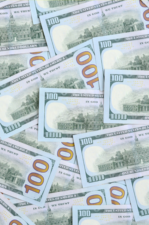 A large number of US dollar bills of a new design with a blue stripe in the middle. Top view.