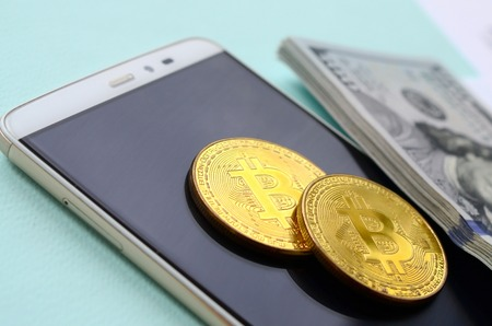 Bitcoins lies with the tax forms, hundred dollar bills and smartphone on a light blue background. Income tax return. Stock Photo