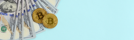 Golden bitcoins and hundred dollar bills lies on light blue background. Stock Photo