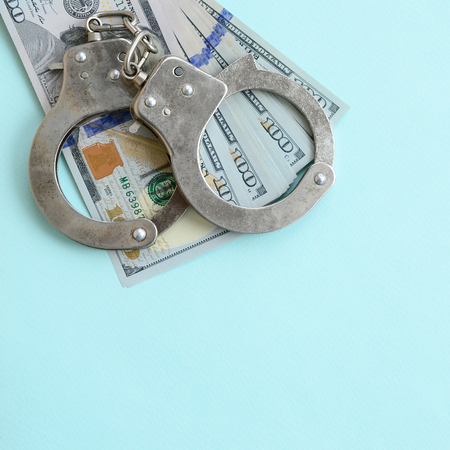 Silver police handcuffs and hundred dollar bills lies on light blue background.