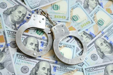 Silver police handcuffs lies on a many dollar bills.