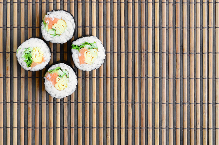 Sushi rolls lies on a bamboo straw serwing mat. Traditional Asian food. Top view. Flat lay minimalism shot with copy space. Stock Photo