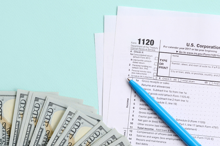 1120 tax form lies near hundred dollar bills and blue pen on a light blue background. US Corporation income tax return. Stockfoto